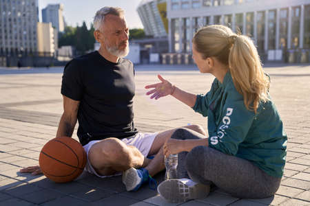 Middle aged couple, active man and woman in sportswear talking while relaxing after basketball workout outdoors on a sunny day