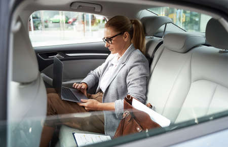Working in taxi. Side view of a successful business woman wearing eyeglasses using laptop while sitting on back seat in the car