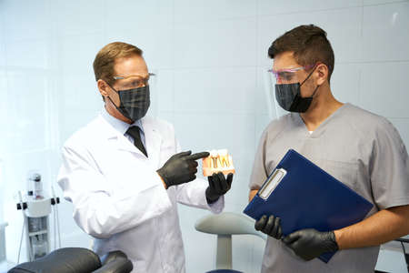 Two dentists talking about anatomy of jaws at the office