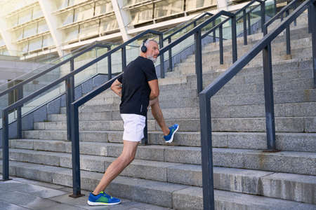 Active middle aged man in headphones looking away while warming up outdoors, getting ready for morning workout in the city Banque d'images