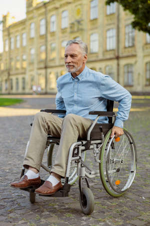 Active mature recovering man in wheelchair smiling away while spending time alone in the park near hospital