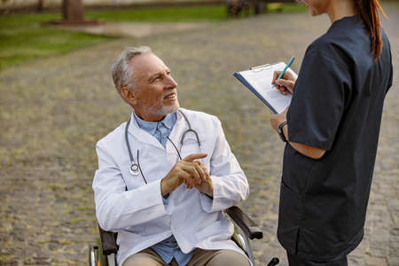 Smiling senior handicapped male doctor in wheelchair wearing lab coat having conversation with nurse making notes while assisting him outdoors