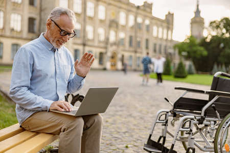Senior man, recovering patient with wheelchair having video call, working on a laptop while sitting on the bench in the park near clinic