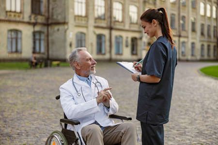 Successful senior handicapped male doctor in wheelchair wearing lab coat talking to young nurse making notes while assisting him outdoors