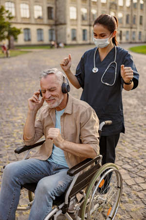 Young nurse in protective mask taking care of senior recovering patient in wheelchair wearing headphones and listening to music outdoors in the park near clinic