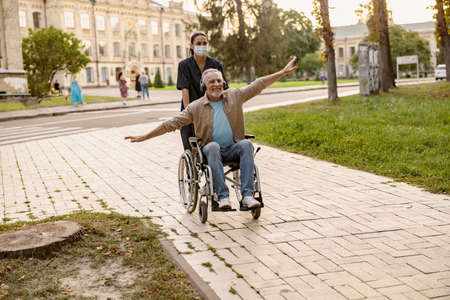 Excited mature disabled man in wheelchair wearing headphones having fun during a walk in the city assisted by young nurse in protective face mask