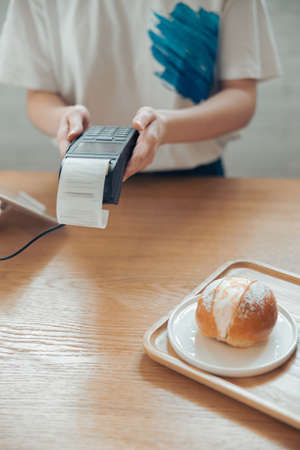 Female barista using terminal for contactless payment in coffee shop Banque d'images