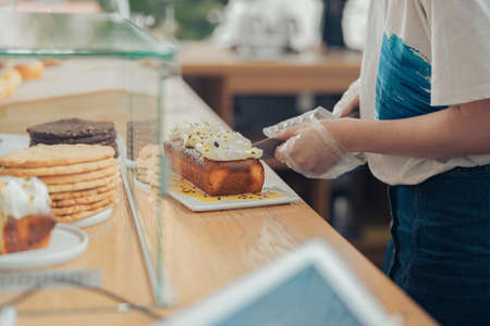 Young woman cutting cake in bakery shop
