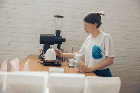 Charming young woman making filter coffee in cafeteria