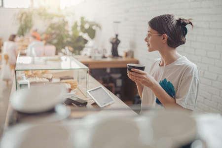 Nice young woman drinking coffee in coffee shop