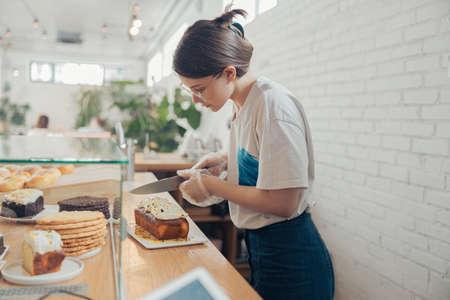 Beautiful young woman cutting cake in bakery shop