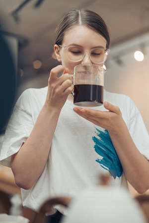 Beautiful young woman smelling coffee in cafeteria Banque d'images