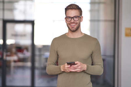 Businessman in glasses holding cellphone and waiting for ring