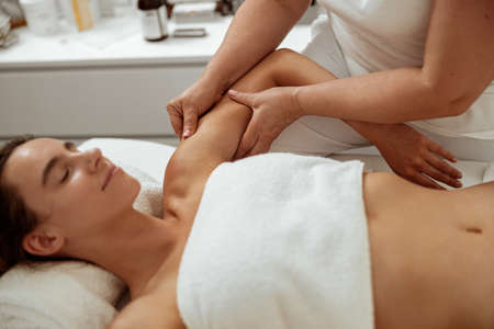 Beautiful young woman receiving professional massage in spa salon