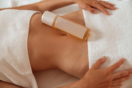 Young woman with cosmetic product on her belly resting in spa salon Banque d'images