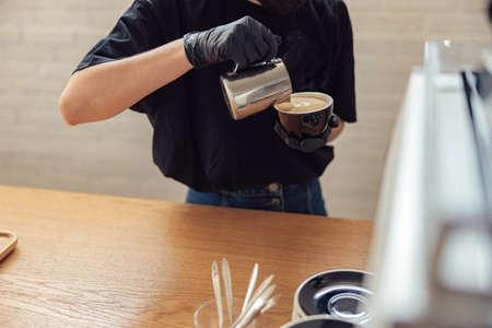 Professional barista is making fresh takeaway latte
