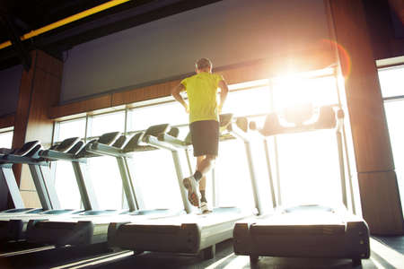 Cardio workout. Rear view of a mature athletic man in sportswear running on a treadmill in a gym, full length