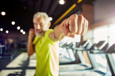 Strength training. Focused mature man in sportswear boxing, while working out at gym, focus on male hand Banque d'images