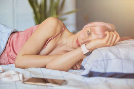 Pretty woman awakes in modern comfortable bed in hotel room