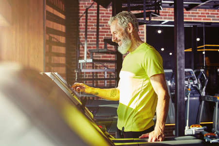 Cardio workout. Side view of a happy middle aged athletic man in sportswear adjusting speed on a treadmill while exercising in a gym or sport club
