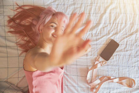 Playful woman hides from camera closing lens by palm on comfortable bed Banque d'images