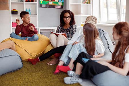 Female teacher sitting on a pouf and reading for schoolchildren
