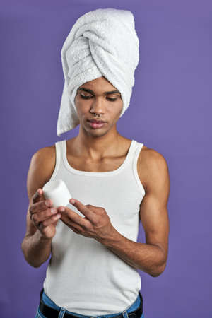 Transgender young man with face cream in hand and towel on head portrait