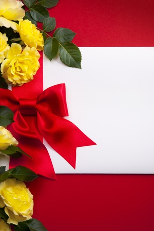 Invitation decorated bow and a bouquet of roses on red Background photo