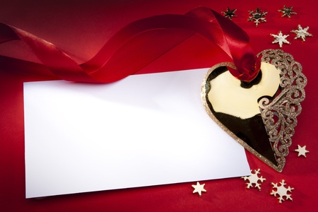Christmas decoration Golden Heart with red ribbon on red background photo