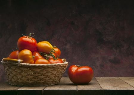 tabulka: červená rajčata v košíku na tmavém pozadí Reklamní fotografie