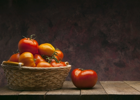 red tomatoes in basket on dark background photo