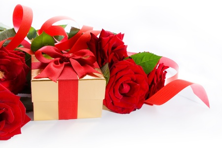 golden gift box and red roses on a white background photo