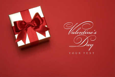 gift background: golden gift box with a red bow on red background