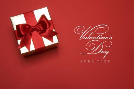 gouden geschenk doos met een rode strik op rode achtergrond Stockfoto