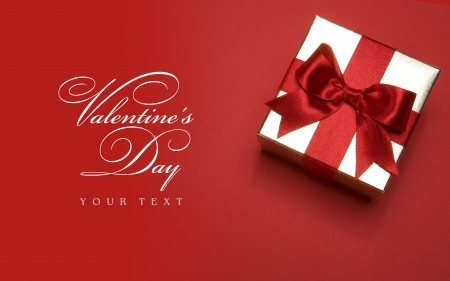 golden gift box with a red bow on red background photo
