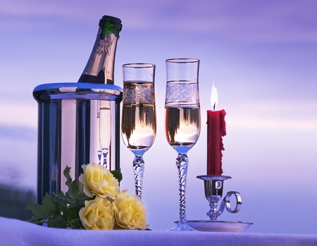 candle light dinner: romantic view with champagne and candles burning in the sky