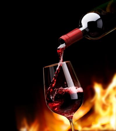 wine pouring: versando vino accanto al caminetto Archivio Fotografico