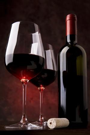 bouteille de vin: vin rouge dans deux verres sur un fond rouge