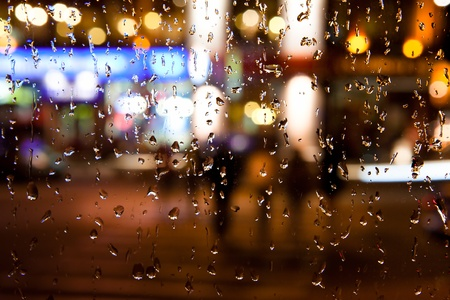 city by night: Wet the window with the background of the autumn night city Stock Photo