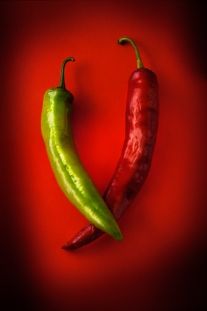 pod is very hot green pepper on a red background photo