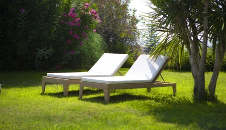 chaise lounges by the pool, summer holidays Stock Photo - 10656925