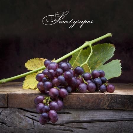 vid: Un racimo de uvas con hojas de color p�rpura tendido en un fondo de madera Foto de archivo