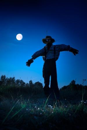 espantapajaros: hombre de paja de pie en un campo de otoño, noche de luna en Halloween