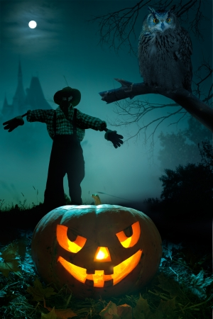 Scary pumpkin, scarecrow and owl near the castle on Halloween night photo