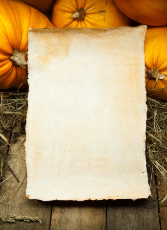 orange pumpkins and  sheet of paper on wooden background photo