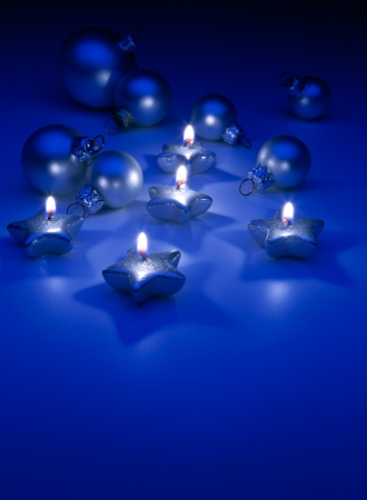 burning Christmas candles and ornaments on a blue background photo