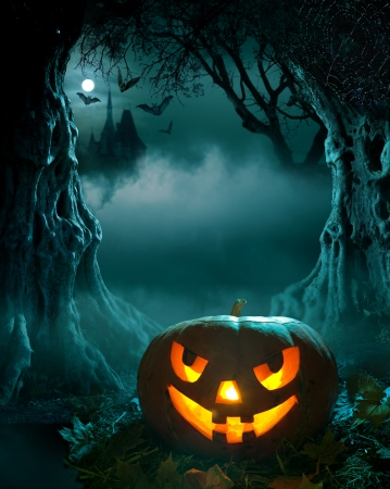 Halloween design, glowing pumpkin in a dark scary forest church photo