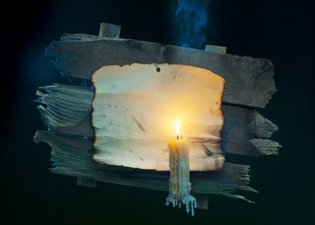 burning paper: halloween background; Old paper and a burning candle on a wooden background  Stock Photo