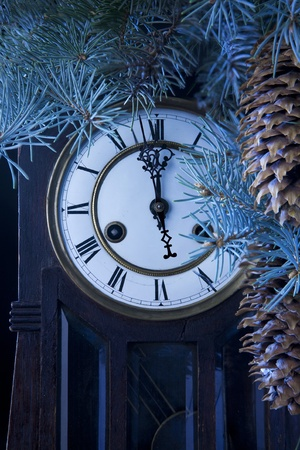 midnight antique clock and a Christmas tree with pine cones photo