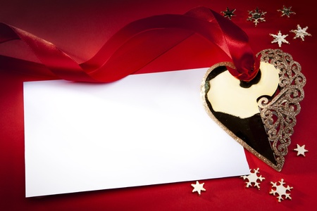 golden heart: Christmas decoration Golden Heart with red ribbon on red background Stock Photo